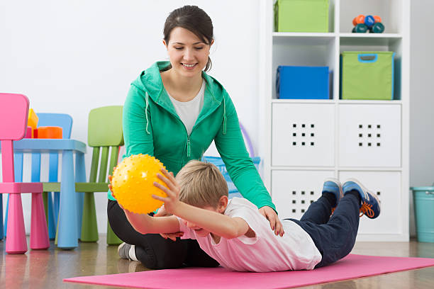 Boy exercising with small gym ball and his smiling instructor